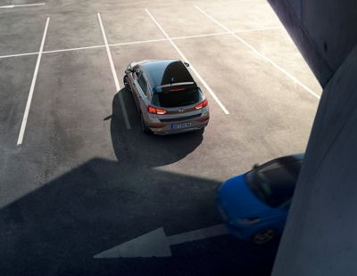 Rear view of the new Hyundai i30 backing out of an empty parking lot.