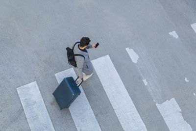 Man with smartphone crossing the street: Hyundai Last Mile Guidance.